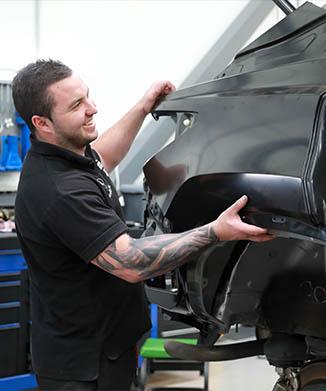 parramatta smash repair technician fitting side panel on car
